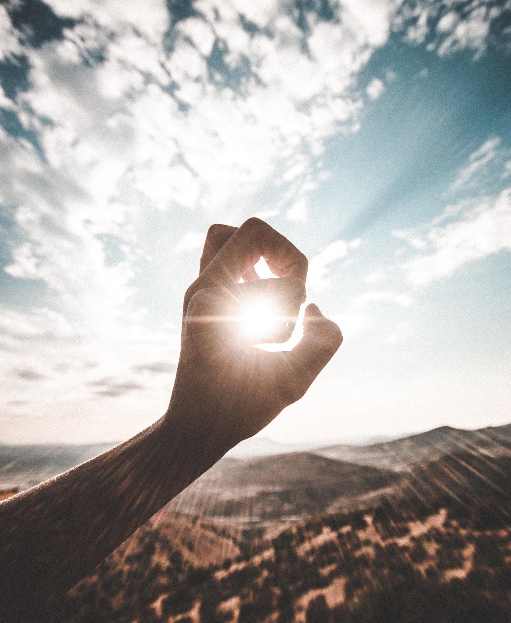 main qui encadre le soleil